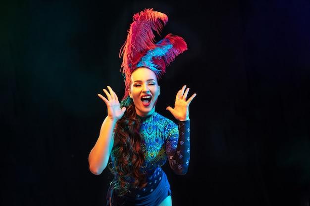Sorprendido. hermosa mujer joven en carnaval, elegante disfraz de mascarada con plumas sobre fondo negro en luz de neón.