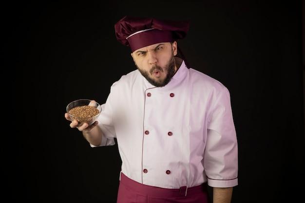Sorprendido hombre barbudo chef en uniforme tiene tazón transparente con trigo sarraceno