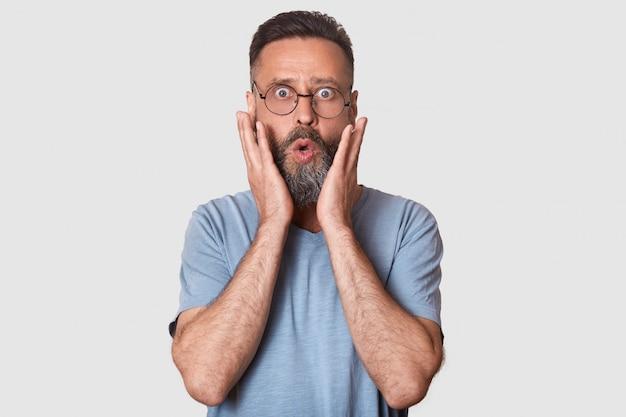 Sorprendido hombre caucásico de mediana edad con gafas y labios redondeados, vestido con camisa gris, se para sobre blanco, tiene expresiones asombradas, mantiene las manos en las mejillas. concepto de personas y emociones.