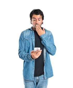 Sorprendido hombre hablando con móvil sobre fondo blanco