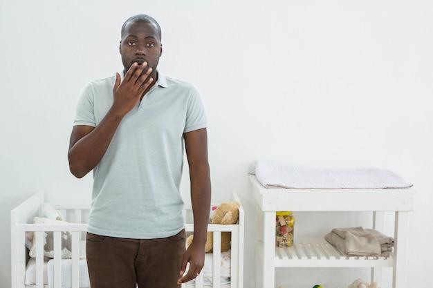 Sorprendido hombre parado frente a una cuna en casa