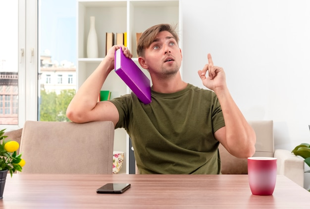 Sorprendido joven apuesto rubio se sienta a la mesa con el teléfono y la taza sosteniendo el libro en el hombro mirando y apuntando hacia arriba dentro de la sala de estar