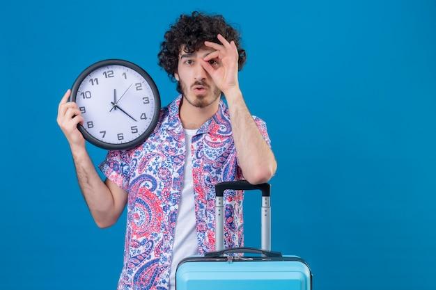 Sorprendido joven apuesto viajero hombre haciendo gesto de mirada sosteniendo el reloj con el brazo en la maleta en la pared azul aislada con espacio de copia