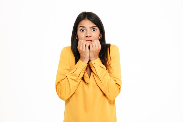 Sorprendido joven asustada en camisa amarilla de pie aislado