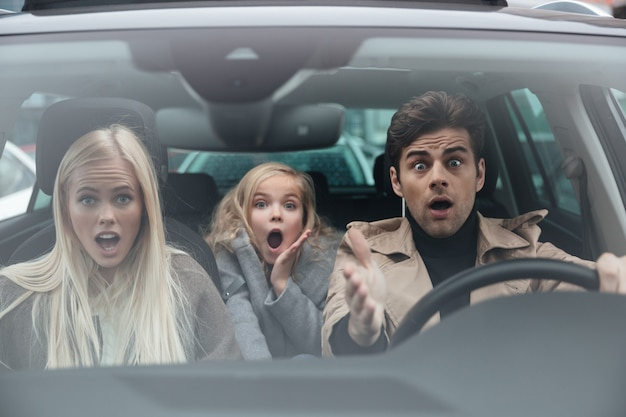 Sorprendido joven asustado sentado en coche con familia