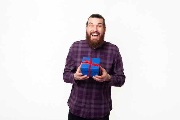 Sorprendido, joven, barbudo, tenencia, caja de regalo azul
