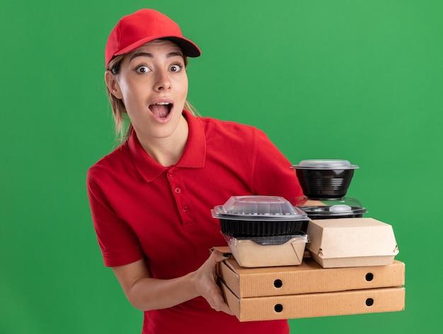 Sorprendido joven bonita repartidora en uniforme sostiene paquetes de alimentos de papel y contenedores en cajas de pizza en verde