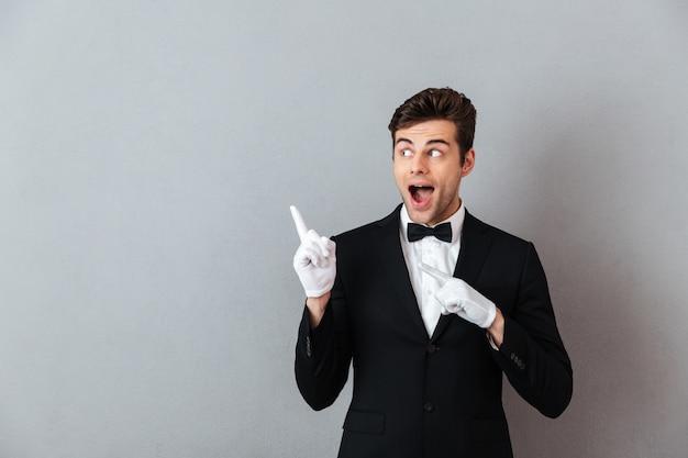 Sorprendido joven camarero señalando.