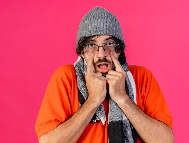 Sorprendido joven caucásico enfermo con gafas sombrero de invierno y bufanda tirando hacia abajo los párpados aislados en la pared carmesí