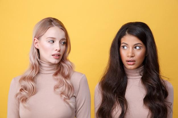Sorprendido joven dos señoras de pie sobre la pared amarilla