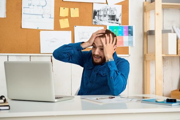 Sorprendido joven empresario exitoso sonriendo, sentado en el lugar de trabajo con ordenador portátil