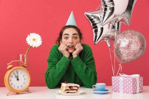 Sorprendido joven estudiante nerd celebrando su cumpleaños mientras está sentado junto a la mesa