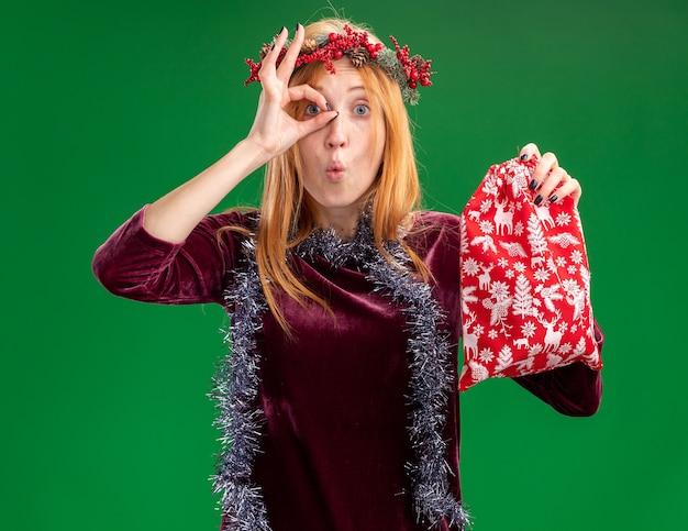 Sorprendido joven hermosa chica con vestido rojo con corona y guirnalda en el cuello sosteniendo una bolsa de navidad mostrando gesto de mirada aislado en la pared verde