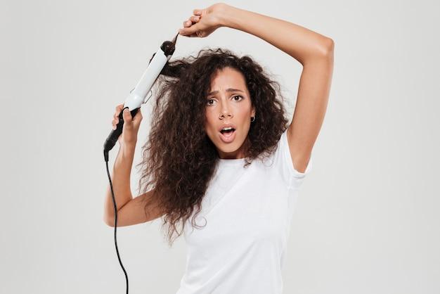 Sorprendido joven mujer morena enderezar su cabello y mirando la cámara aislada sobre blanco