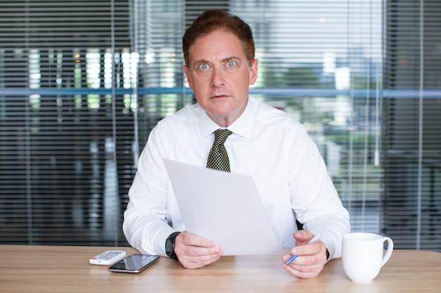 Sorprendido, maduro, hombre de negocios, trabajando, escritorio