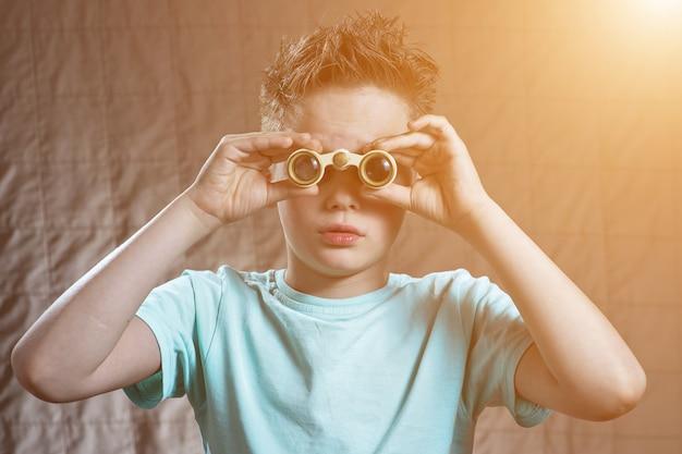 Sorprendido muchacho adolescente emocionalmente mirando a través de binoculares