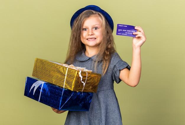 Sorprendido niña rubia con gorro de fiesta azul sosteniendo cajas de regalo y tarjeta de crédito aislado en la pared verde oliva con espacio de copia