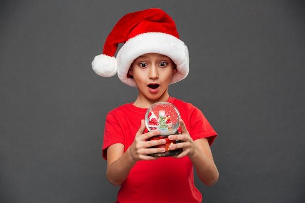Sorprendido niño niño con sombrero de navidad santa