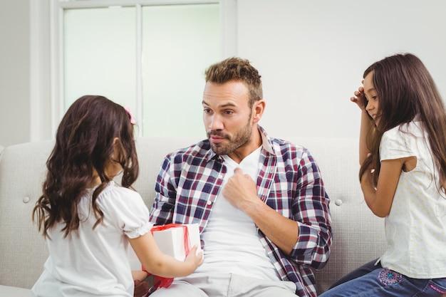 Sorprendido padre mirando a su hija con un regalo