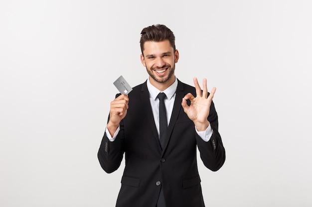 Sorprendido, sin palabras e impresionado apuesto hombre de negocios caucásico en traje clásico mostrando tarjeta de crédito, digamos wow, de pie asombrado