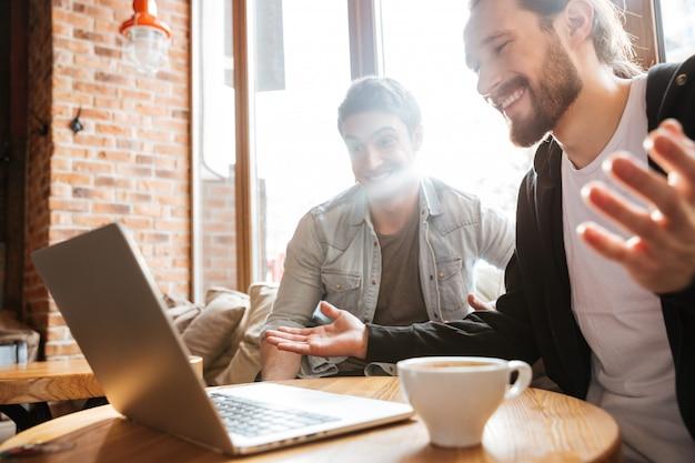 Sorprendidos amigos sonrientes con laptop en café