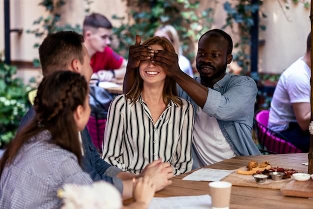 Sorpresa de un amigo africano a una niña caucásica en la terraza al aire libre de un restaurante