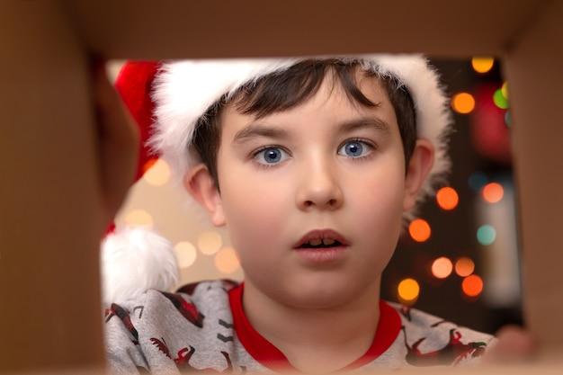 Sorpresa de emoción en un niño con un jersey de año nuevo y un sombrero de santa claus mira en una caja con un regalo, una vista desde el interior, sobre un fondo