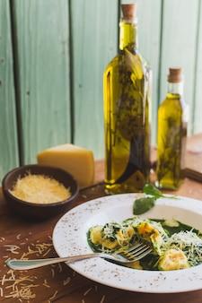 Sorrentino con queso parmesano y aceite de oliva en una mesa de madera