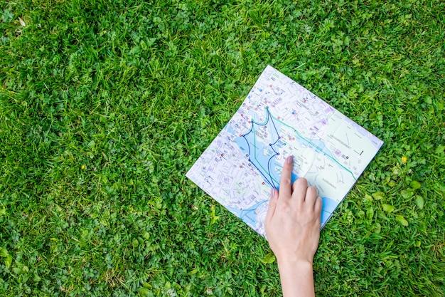 Dé sostener una hoja de papel con el mapa del viaje sobre fondo verde de la naturaleza del bosque.