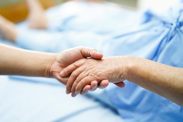 Sostener las manos asiáticas mayores o ancianas ancianas mujer paciente con amor