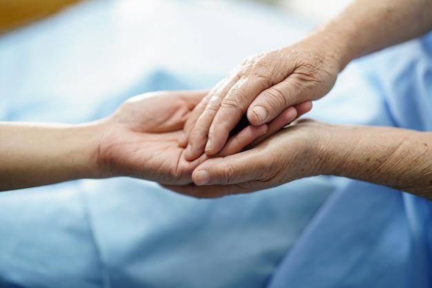 Sostener las manos asiáticas mayores o ancianos anciana mujer paciente con amor