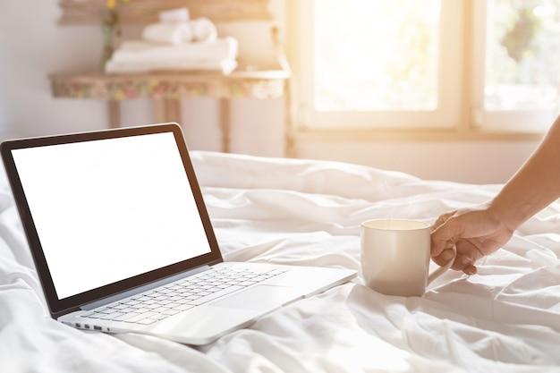 Dé sostener la taza de café y el ordenador portátil en la cama en el tiempo de mañana, foco en la mano
