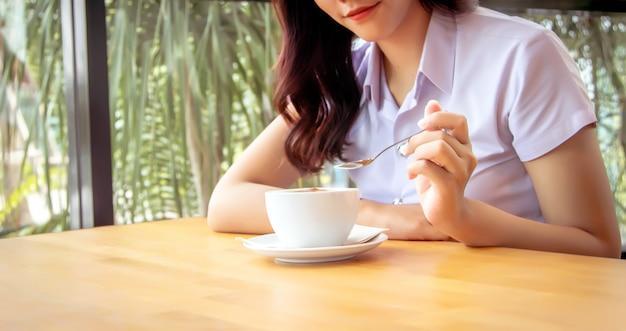 Sostenga la cuchara con la mano para mezclar la espuma de café caliente en una taza de cerámica