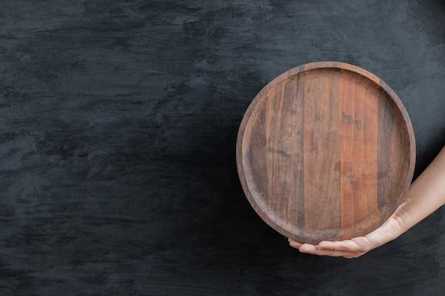Sosteniendo una bandeja circular de madera con la mano