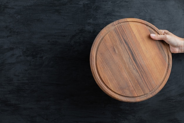 Sosteniendo una bandeja de madera redonda en la mano