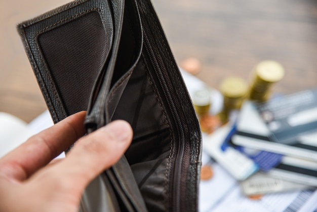 Sosteniendo una billetera vacía en la mano y la moneda