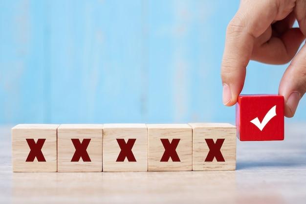 Sosteniendo el bloque de cubos de madera con el símbolo correcto diferente del símbolo incorrecto