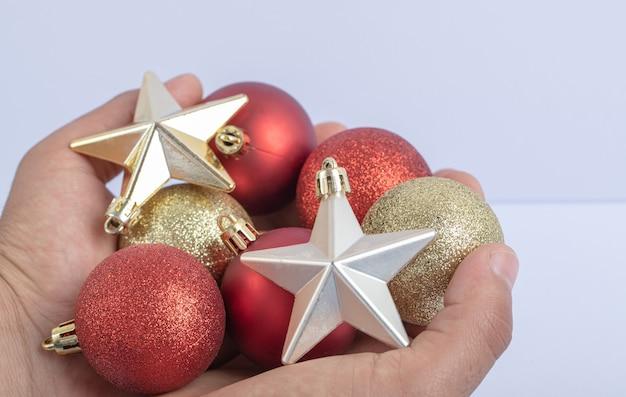 Sosteniendo bolas de árbol de navidad y estrellas en la mano