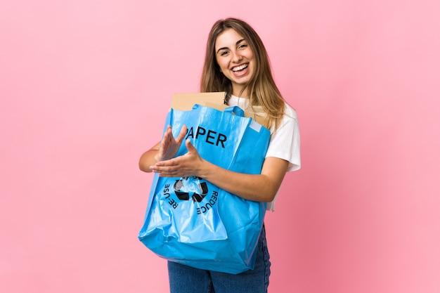 Sosteniendo una bolsa de reciclaje llena de papel para reciclar sobre aplausos rosados aislados