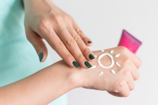 Sosteniendo la botella de protector solar con crema como forma de sol en la mano