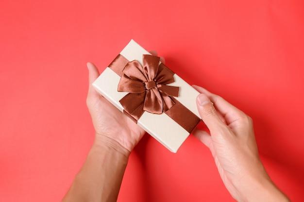 Sosteniendo una caja de regalo con las dos manos.