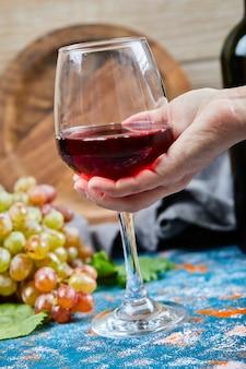 Sosteniendo una copa de vino tinto sobre una mesa azul con un racimo de uvas