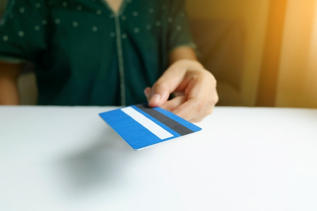 Sosteniendo y dando la tarjeta de crédito. compras en línea, negocios en línea