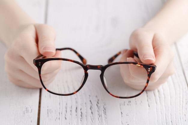 Sosteniendo gafas en manos femeninas