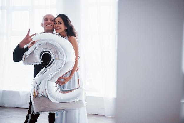 Sosteniendo el globo de color plateado en la forma del número dos. joven pareja en ropa de lujo se encuentra en la sala blanca
