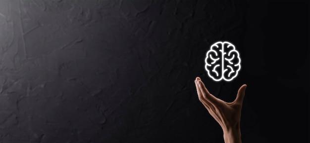 Sosteniendo el icono de cerebro sobre fondo azul. inteligencia artificial machine learning business internet