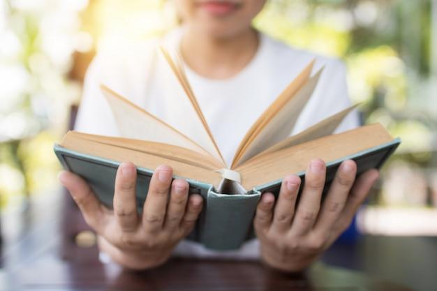 Sosteniendo el libro abierto en dos manos sobre la mesa, el concepto de sabiduría y conocimiento