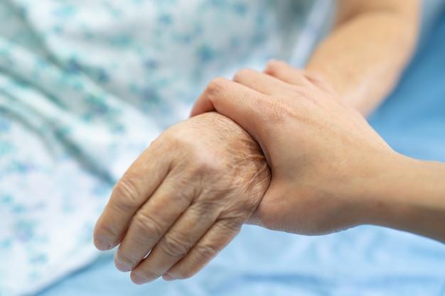 Sosteniendo la mano paciente mayor asiático de la mujer con amor.