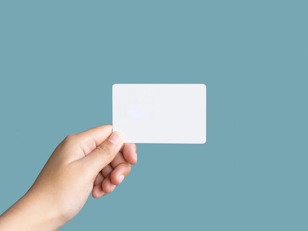 Sosteniendo maqueta de tarjeta de visita blanca en color pastel