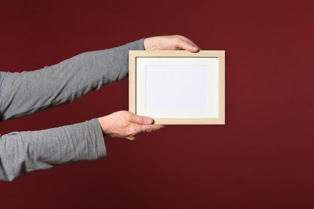 Sosteniendo un marco de madera sobre fondo rojo.